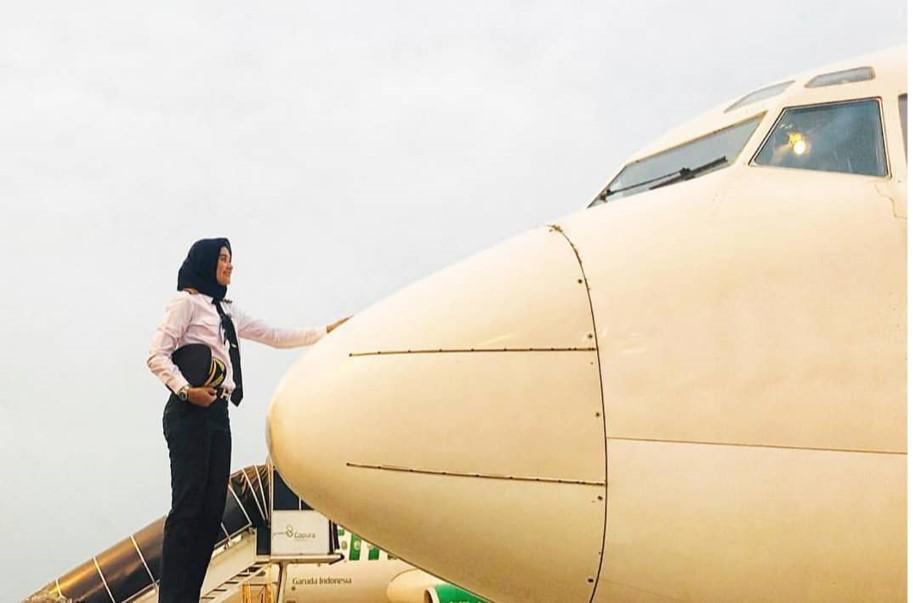 Seorang pilot wanita di depan sebuah pesawat terbang